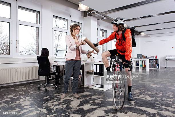 Germany, Bavaria, Munich, Courier man giving parcel to woman in office