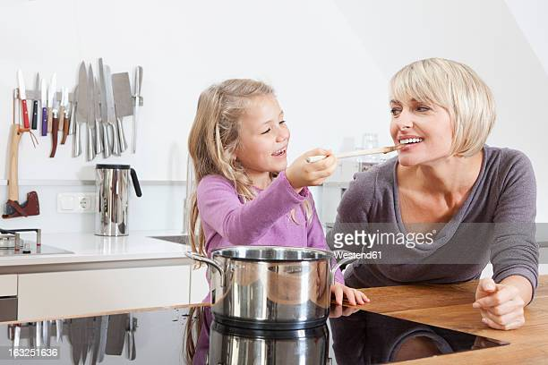 Germany, Bavaria, Munich, Daughter feeding mother in kitchen, smiling