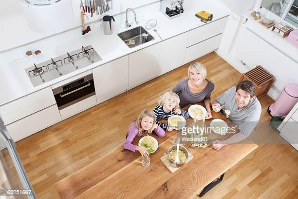 Germany, Bavaria, Munich, Family eating spaghetti in kitchen