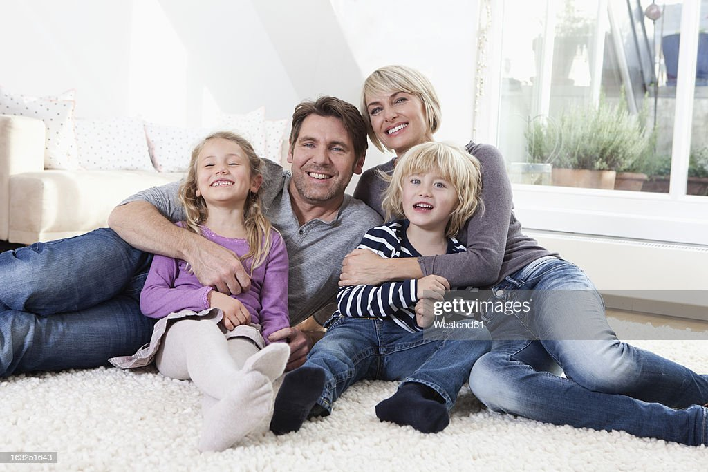 Germany, Bavaria, Munich, Family lying on floor, portrait, smiling : Stock Photo