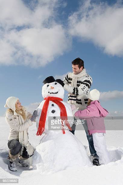 Germany, Bavaria, Munich, Parents with daughter (6-7) making snowman