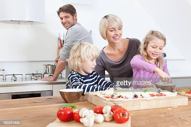 Germany, Bavaria, Munich, Family preparing pizza in kitchen