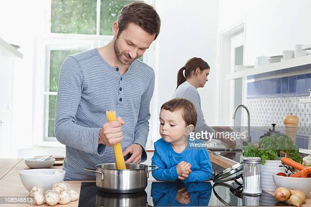Germany, Bavaria, Munich, Father and son (2-3 Years) cooking spaghetti and mother in background