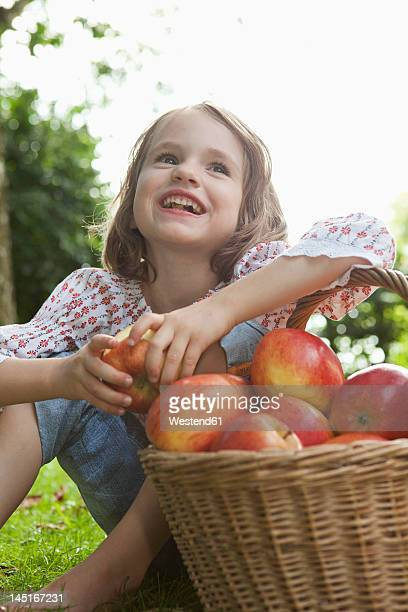 Germany, Bavaria, Munich, Girl sitting with basket of apples