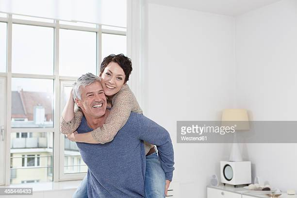 Germany, Bavaria, Munich, Man giving piggy back ride to woman, smiling