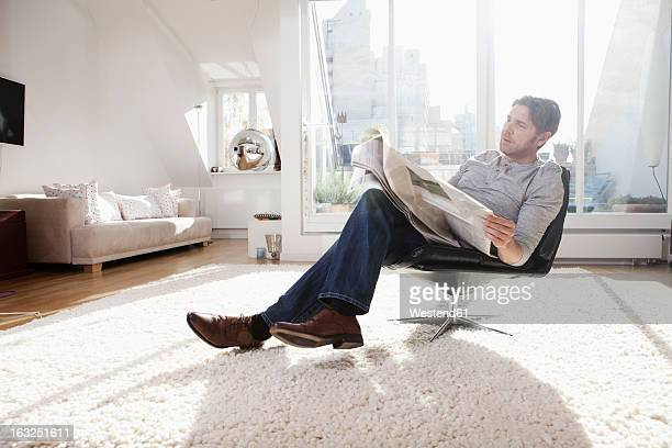 Germany, Bavaria, Munich, Man reading newspaper in living room
