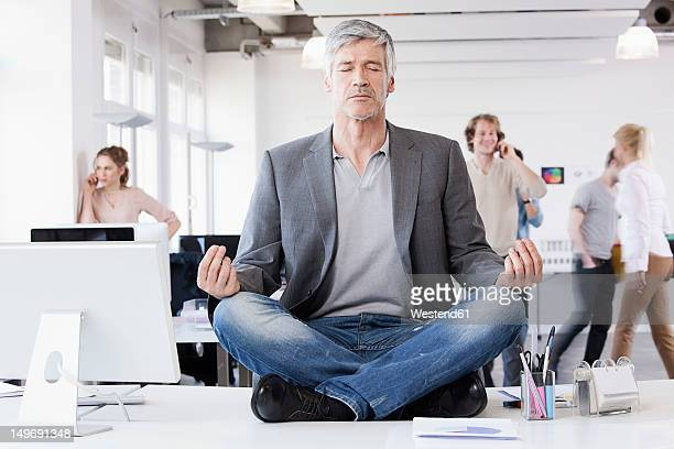 Germany, Bavaria, Munich, Man sitting in lotus position, colleagues in background
