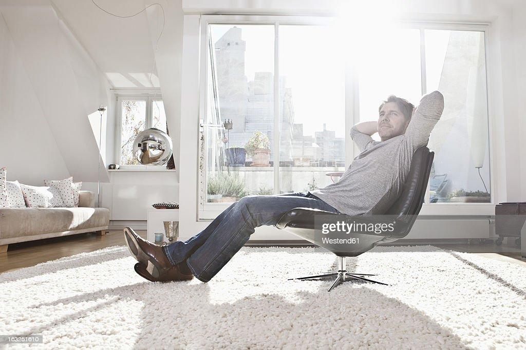 Germany, Bavaria, Munich, Man sitting on armchair : Stock Photo
