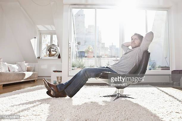 Germany, Bavaria, Munich, Man sitting on armchair