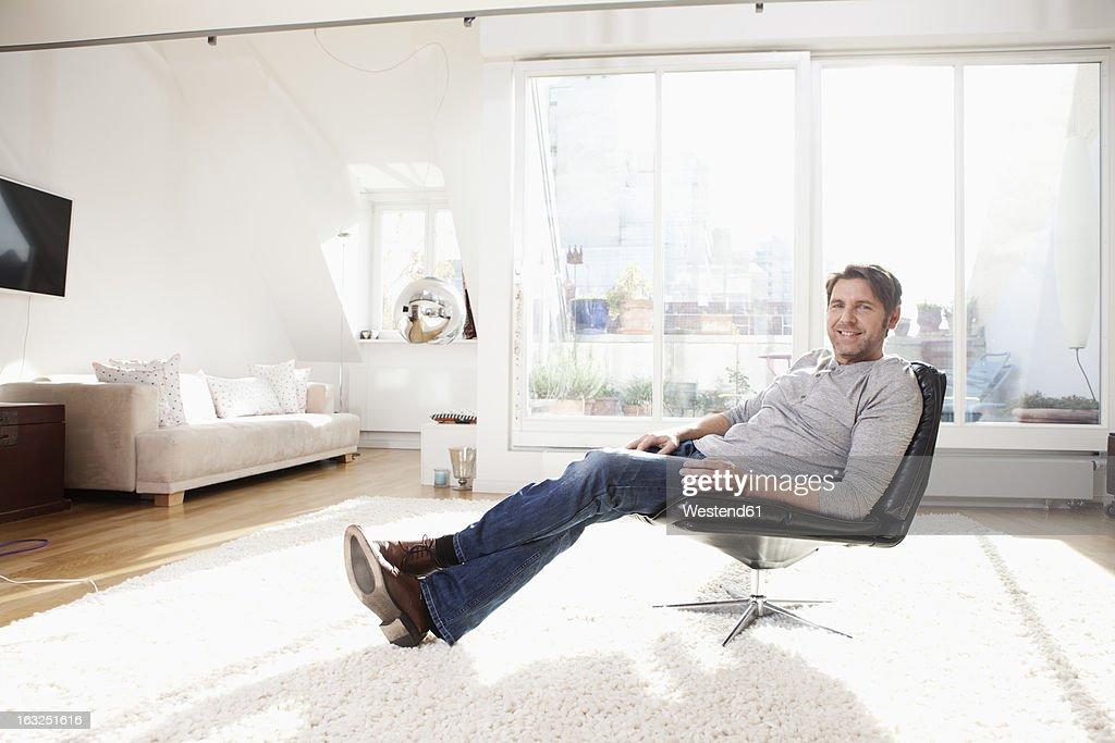 Germany, Bavaria, Munich, Man sitting on chair, smiling