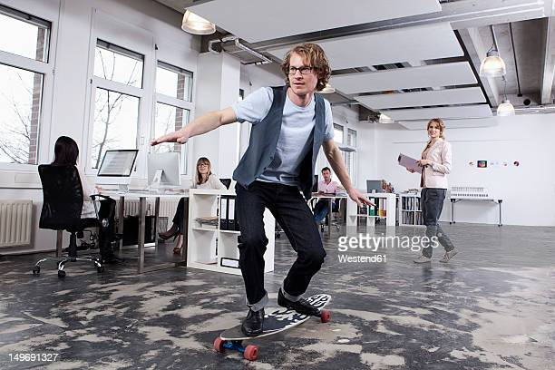 Germany, Bavaria, Munich, Man skate boarding in office while colleagues working in background
