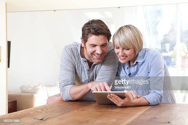 Germany, Bavaria, Munich, Mature couple using digital tablet, smiling