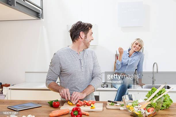 Germany, Bavaria, Munich, Mature man chopping vegetables, woman sitting in background