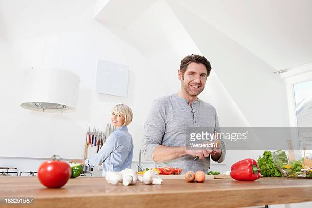 Germany, Bavaria, Munich, Mature man chopping vegetables, woman standing in background