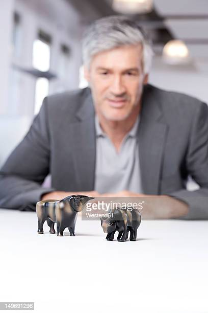 Germany, Bavaria, Munich, Mature man looking at bull and bear figurines
