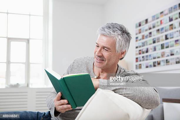 Germany, Bavaria, Munich, Mature man reading book on couch, smiling