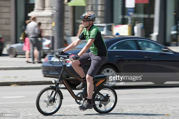 Germany, Bavaria, Munich, Mature man riding electric bicycle