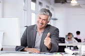 Germany, Bavaria, Munich, Mature man showing thumbs up, colleagues working in background