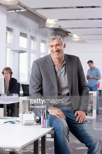 Germany, Bavaria, Munich, Mature man smiling, colleagues in background : Stock Photo