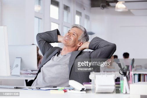 Germany, Bavaria, Munich, Mature man smiling, colleagues working in background : Stock Photo