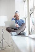 Germany, Bavaria, Munich, Mature man talking on mobile and using laptop, smiling
