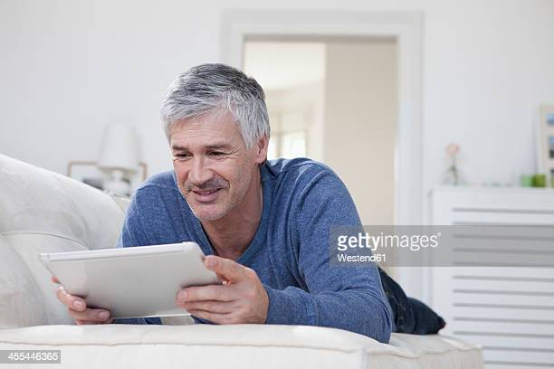 Germany, Bavaria, Munich, Mature man using digital tablet on couch, smiling
