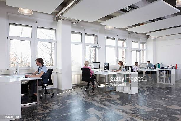 Germany, Bavaria, Munich, Men and women working on computer in office