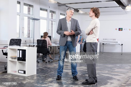 Germany, Bavaria, Munich, Men discussing, colleagues in background : Stock Photo