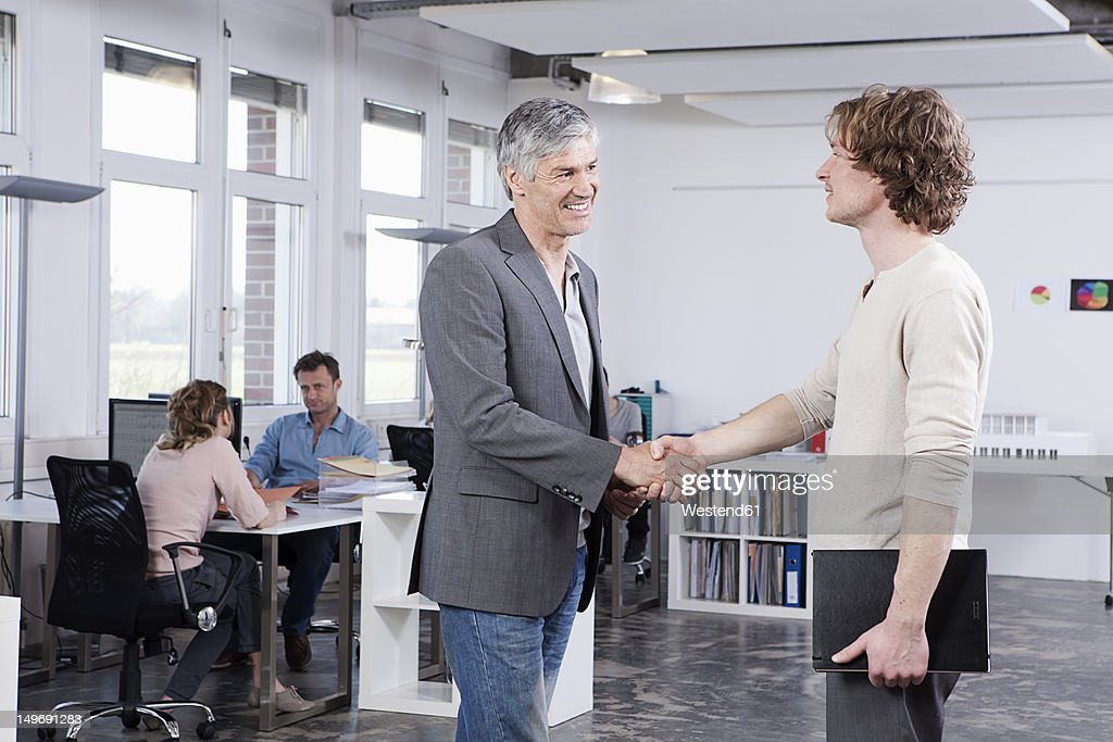 germany bavaria munich men shaking hands while colleague
