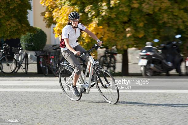 Germany, Bavaria, Munich, Mid adult woman riding electric bicycle