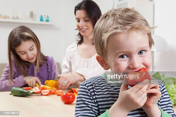 Germany, Bavaria, Munich, Mother and daughter preparing salad, son eating