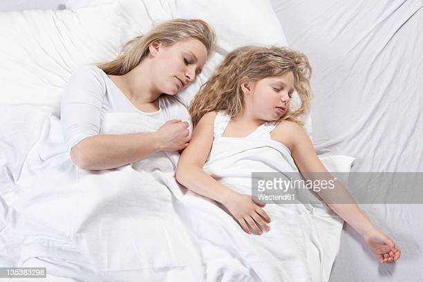 Germany, Bavaria, Munich, Mother and daughter sleeping on bed