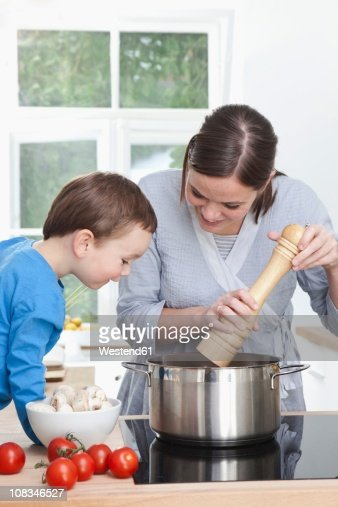 Germany, Bavaria, Munich, Mother and son (2-3 Years) preparing meal in kitchen : Stock Photo