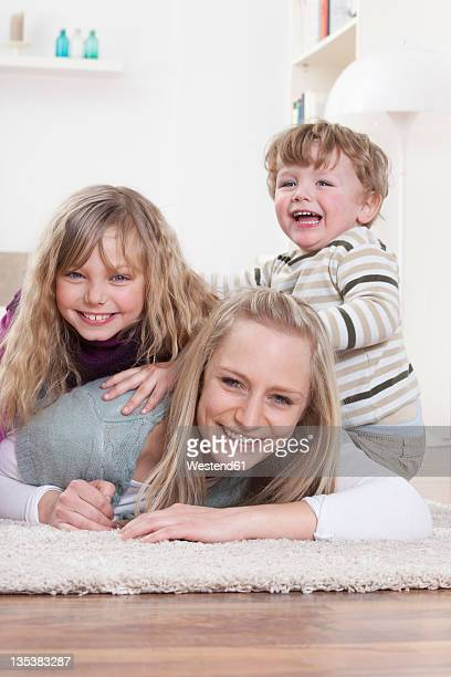 Germany, Bavaria, Munich, Mother, daughter and son lying on floor at home