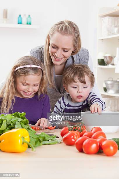 Germany, Bavaria, Munich, Mother, daughter and son preparing salad