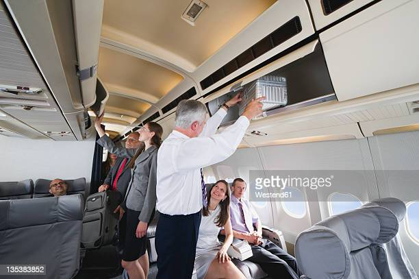 Germany, Bavaria, Munich, Passengers removing hand luggage from shelf in business class airplane cabin