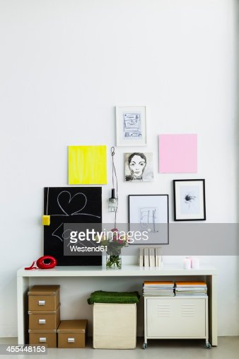 Germany, Bavaria, Munich, Picture frame hanging on wall with flower vase and telephone on shelf