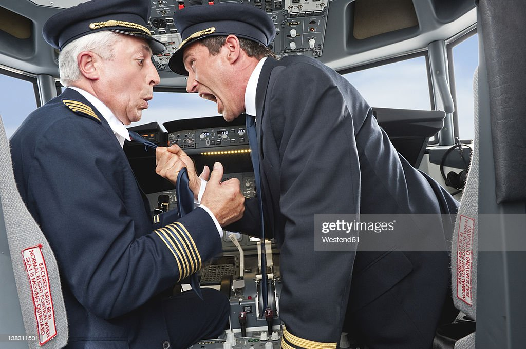 Germany, Bavaria, Munich, Pilot and co-pilot fighting in airplane cockpit