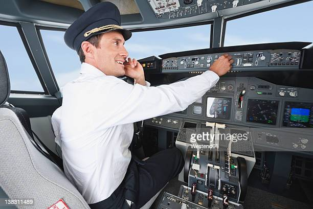 Germany, Bavaria, Munich, Pilot using mobile phone and piloting aeroplane from airplane cockpit