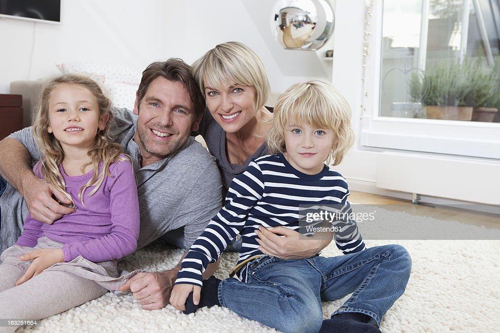 Germany, Bavaria, Munich, Portrait of family lying on floor, smiling : Stock Photo