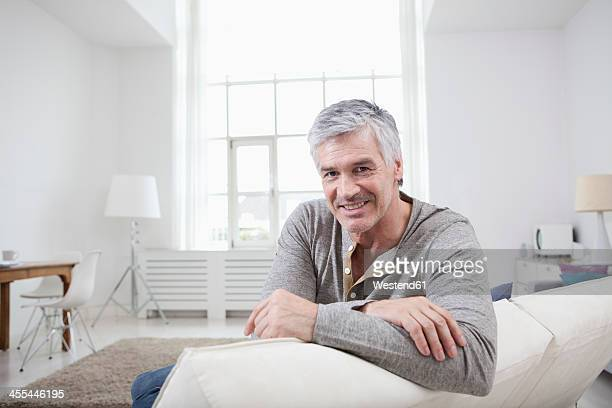 Germany, Bavaria, Munich, Portrait of mature man sitting on couch, smiling