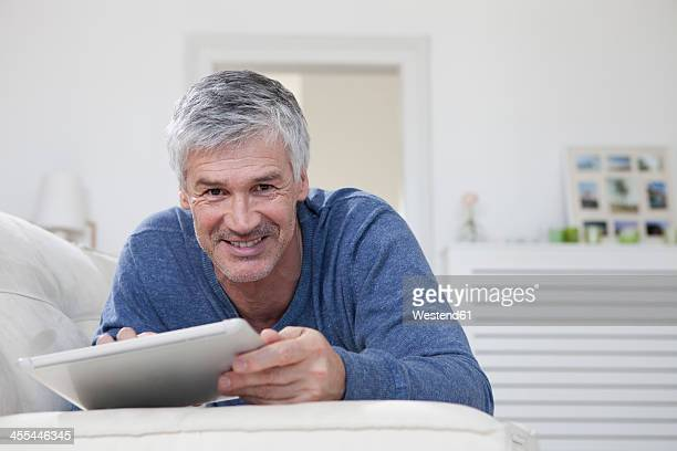 Germany, Bavaria, Munich, Portrait of mature man using digital tablet on couch, smiling