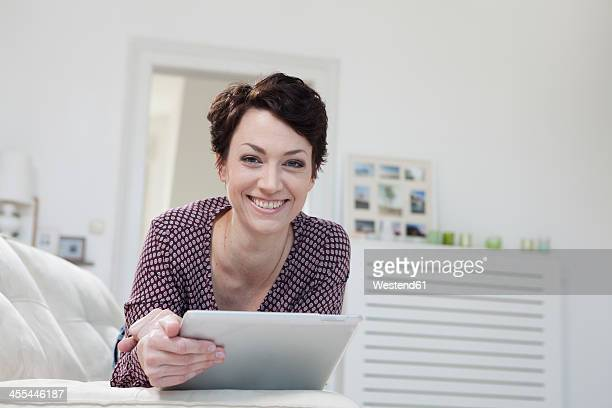 Germany, Bavaria, Munich, Portrait of mid adult woman using digital tablet on couch, smiling