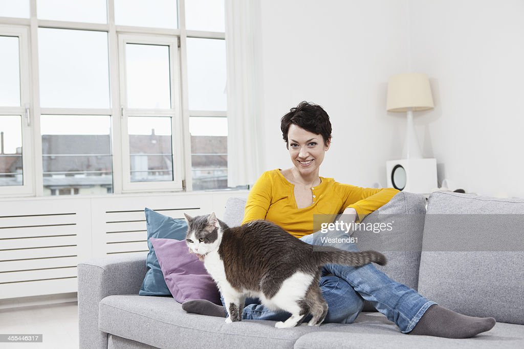 Germany, Bavaria, Munich, Portrait of mid adult woman with cat on couch, smiling : Stock Photo