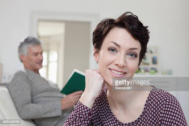 Germany, Bavaria, Munich, Portrait of woman smiling while man reading book in background