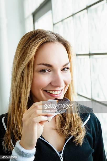 Germany, Bavaria, Munich, Portrait of young woman eating chocolate, smiling
