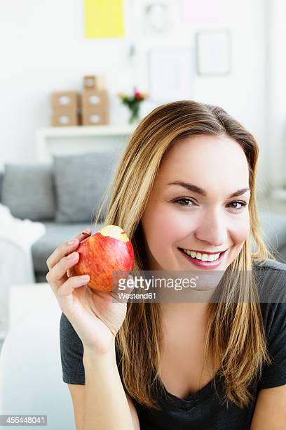 Germany, Bavaria, Munich, Portrait of young woman holding apple, smiling