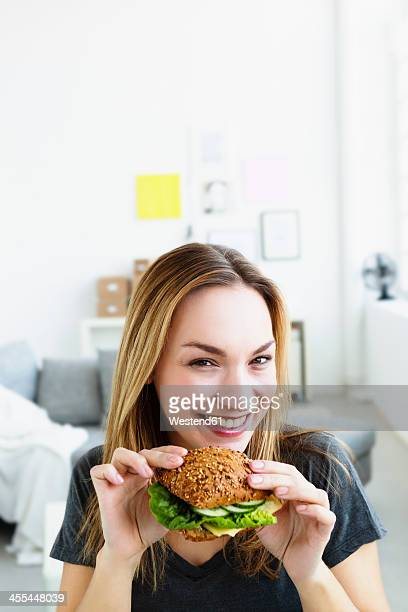 Germany, Bavaria, Munich, Portrait of young woman holding sandwich, smiling