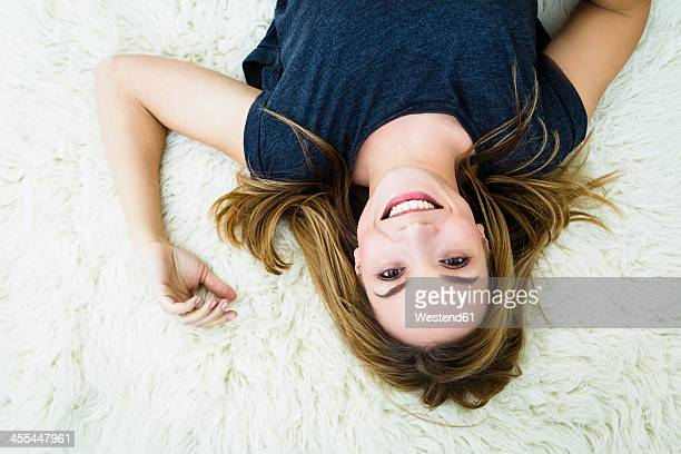 Germany, Bavaria, Munich, Portrait of young woman lying on carpet, smiling