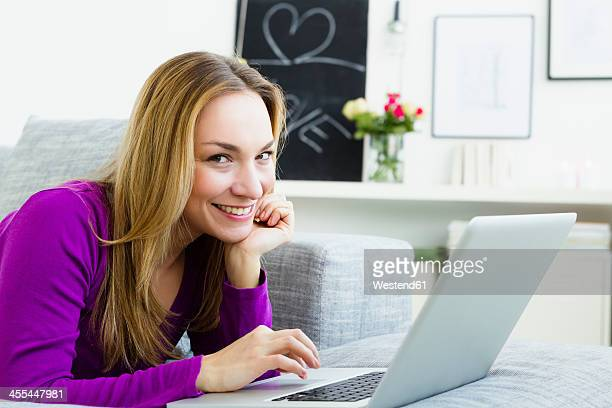 Germany, Bavaria, Munich, Portrait of young woman using laptop, smiling